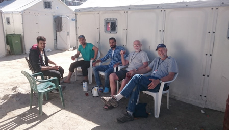 Volunteers having tea with refugees in Lesbos camp